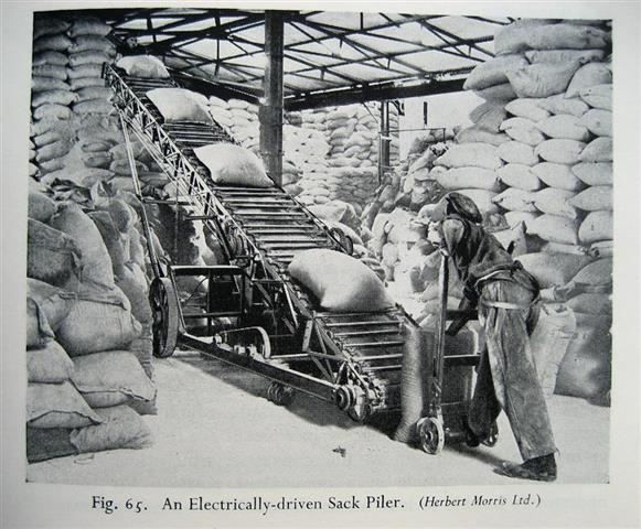 In the early 1900s, factory workers were experiencing an increasing availability of material handling implements such as this hand truck and electrically-driven sack piler.